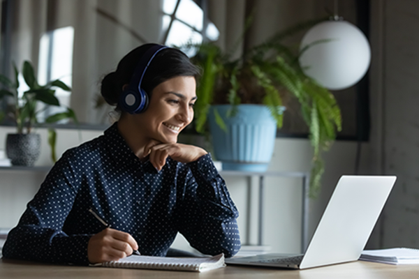 woman-smiling-at-computer-wearing-headphones